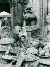 Fruit seller siting with his child.