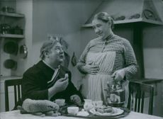 "A scene in 1936 film "" Johan Ulfstjerna"" Bjorn Berglund sitting on the table eating while Jullan Jonsson serving him as she holds a kettle."