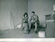 Claude Brasseur sits with a woman on his side, 1961.