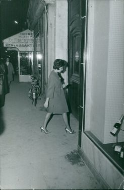 A woman walking and about to enter a restaurant, 1963.