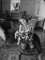 Lee Ann Remick sitting with a bouquet.