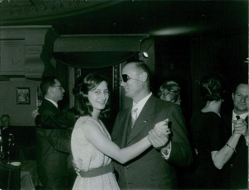 Yaël Dayan is dancing with his father former Israeli military leader and politician Moshe Dayan, Yael smiling and looking towards the camera