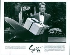 "A photo of a man holding a gift in a film ""Sabrina""."
