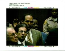 OJ Simpson waves a defence team and listens to verdict of not guilty murder trial.