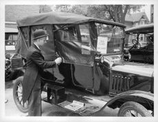 Man standing by Ford Model T.