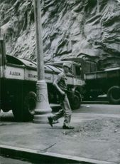Soldier walking holding gun, army trucks siege the road.