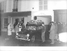 Car decorated with white flowers, people watching.