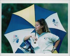 Golf player Nick Faldo's caddy Fanny Sunesson with an umbrella under the Ryder Cup in 1995