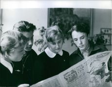 Boys and girls reading a Russian newspaper.