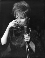 A woman drinking wine while holding a microphone.