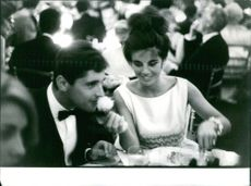 Sacha Distel and a woman dining. Photo taken Oct 2, 1962