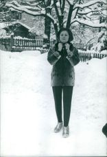 A woman standing on snow, wearing scarf.