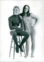 Man siitting on a bar stool  and woman leaning, strike a pose wearing jumpsuit. 1969