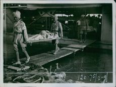 Troops carrying a sick person on a stretcher during First World War, 1916.