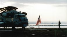 A helicopter next to an American flag