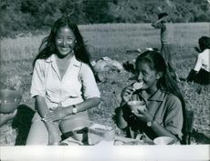 Two women are smiling towards the camera while eating in the land of Nepal.