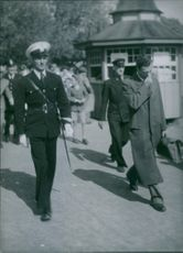Policemen and some civilians walking on the street, 1949.