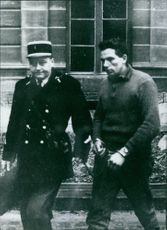Policeman holding and taking away an offender, 1965.
