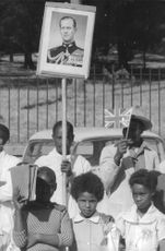 A man holding a placard of Captain Mark Anthony Peter Phillips.