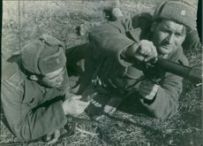 Close up of soldiers lying on ground, pointing gun at someone during wartime.