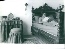 Marielle Goitschel reading a book in bedroom.
