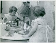 A little girl plays with the bottles that are on a dresser cabinet.