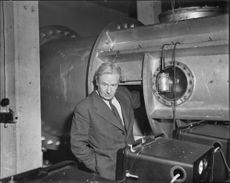 The head of the aerodynamics department, Petersohn, in front of the measuring section of one of the Aeronautical Research Institution current wind tunnels.