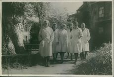 Five women and a man in white clothing are standing outside the house, 1943.
