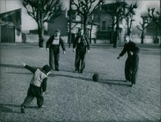 Men standing and playing football with a child. 1949