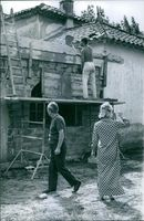 Marcel Pagnol watching over the construction worker do his work on his house. 1964.