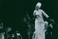 A woman singing on the stage with the band.