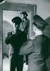 A vintage photo of a soldier fixing his uniform in the mirror, German wartime 1960.