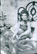 Rosanna Yanni known as Rosanna Yanni or Rossana Yanni, is an Argentine film actress posing in bed and smiling.