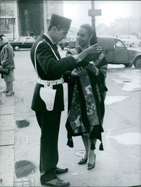 A policeman showing direction of an address to a woman.