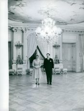 Man and woman standing underneath illuminated chandelier.