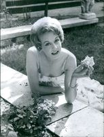 Gisèle Pascal holding a flower and smiling. Photo taken on August 3, 1961.