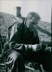1951  A photo of a man siting and holding knife.