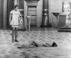 An actor looking at nuyde Pascale Petit lying on a carpet during film shooting.