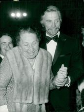 Kirk Douglas helps Berta Litvina in place during the Cannes Film Festival