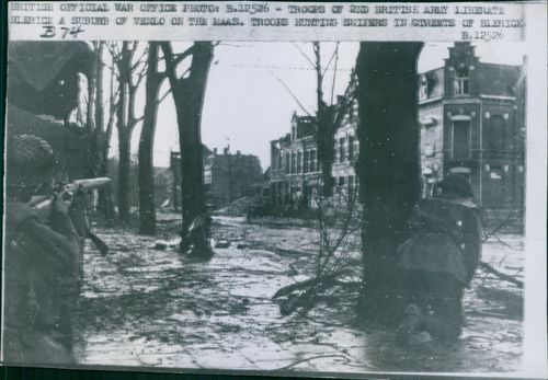 Troops of the second British Army firing and hunting snipers in the street of Blerick.