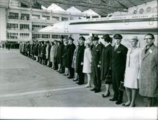 All staff members of British Airways standing together in front of airplane.