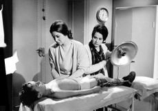 Women looking at the boy with injuries, 1966.