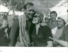 Man embracing woman, several standing behind.