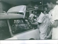 People placing quintuplets in car.