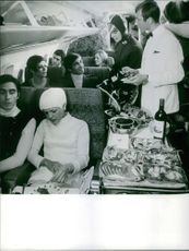 Food being served to the passengers inside of the airplane, 1967.