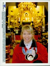 German skier Katja Seizinger poses in front of an altar in a Buddhist temple with his two gold medals from the Winter Olympics 1998