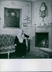 Anna Branting sitting on a couch beside a fireplace, 1945.