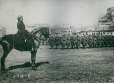 A man in a horse leading troopers.