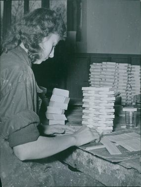 A woman is sitting, and making a paper box on the working table.