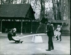 """Couples riding a see-saw, with a man standing in the base of it.  """"Folies Bergère""""  1961"""